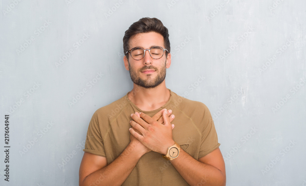 Fototapeta Handsome young man over grey grunge wall wearing glasses smiling with hands on chest with closed eyes and grateful gesture on face. Health concept.