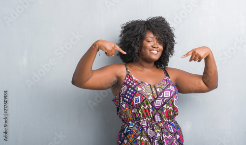 Slika na platnu Young african american woman over grey grunge wall wearing colorful dress looking confident with smile on face, pointing oneself with fingers proud and happy