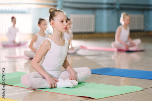 a group of children in a ballet school or in a gymnastics section on carimat rugs perform exercises