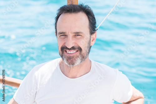 Fotografia  Handsome senior man traveling on sailboat and smiling happy and confident