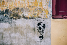 Beautiful Wall Graffiti Artist Illustrated A Balloon With The World Map On It Is Carrying A Lizard And Floating Away. The Background Wall Has Damaged Decayed Paint And Dirty Background.