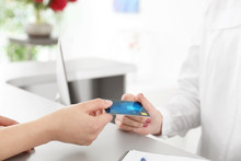 Woman Giving Credit Card To Receptionist At Desk In Beauty Salon, Closeup