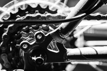 Closeup Image Of The Mechanical Parts Of A Bikes Rear Gear Cog System With The Chain In A Used Condition And The Spokes Of The Frame And The Visible In This Cycling Image.