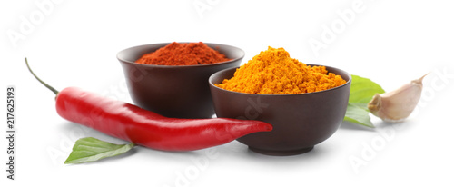 Different aromatic spices in bowls on white background