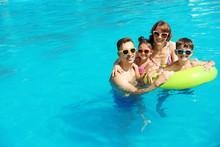Happy Family In Swimming Pool At Resort
