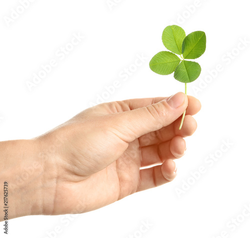 Woman holding four-leaf clover on white background, closeup