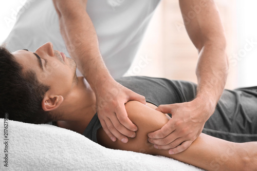 Cuadros en Lienzo  Young man receiving massage in salon, closeup