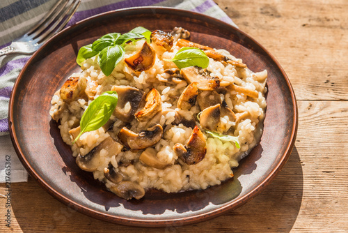 Italian traditional dish - risotto with mushrooms with basil leaves in a clay plate on an old wooden table, top view, copy space for a recipe