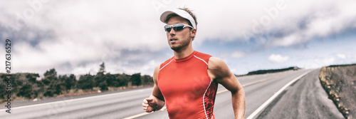 Triathlon runner man running on road panoramic backbround. Fit athlete jogging on competition race. Triathlete training for marathon banner panorama.