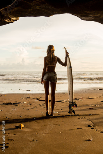 Young surfer girl with surf board pose in cave at beach. Garbage and plastic on sand. Concept of ecological problem and disaster. People water sport adventure camp and extreme swim on summer vacation