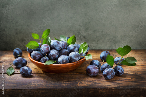 blue plums with leaves in a bowl on wooden table