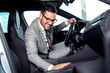 Handsome businessman is sitting in a new car in car dealership