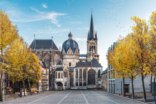 Deurstickers Historisch geb. German cathedral in Aachen during fall with yellow leafs at trees with blue sky