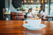 White cup of hot coffee on table in cafe with people. vintage and retro color effect - shallow depth of field