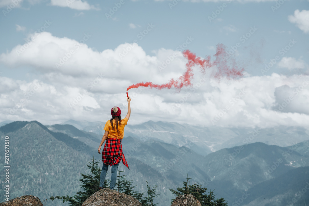 Fototapety, obrazy: Woman on mountain peak with red flare.Inspiration concept.