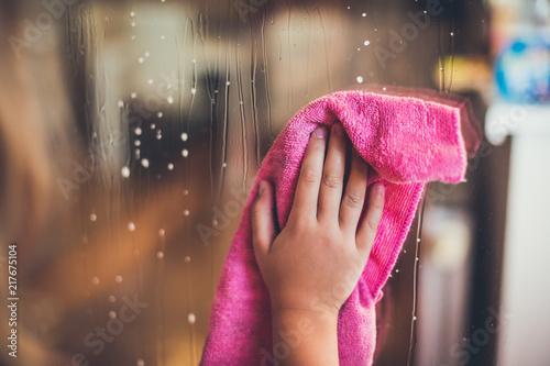 Valokuva  Child's hand wipes the window