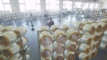 White Fiberglass Coils Unwind Threads In Workshop With Large Windows