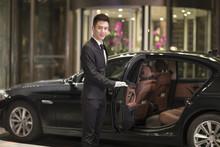 Chauffeur Opening Car Door For Passenger