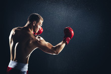 Man Boxing With Red Gloves On His Hands In The Rain.