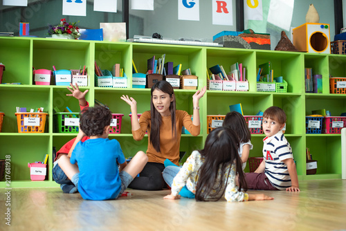 woman teacher in classroom teaching preschool kids, joyful learning together wit Fototapet