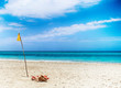 Yellow flag in sand on the beach by the sea. Near is Atlantic ocean. It is situated in Cuba, Caribbean.