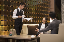 Young Waiter Serving Coffee To Business People