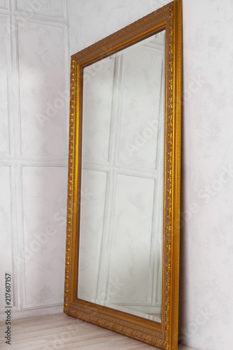 Fotografía Large classic mirror with golden wooden frame side view, home decor