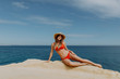 Young sexy woman in red bikini and straw hat lying on the rock edge with ocean background