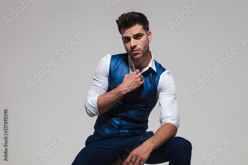 Fotografija seductive man wearing a blue waistcoat holding his collar