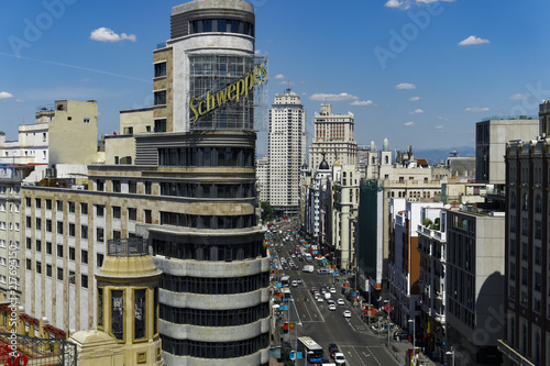 Fototapeta premium Madrid, Spain Gran Via panoramic view. Day traffic view of main shopping street with Carrion building advertisement in the centre of Madrid.