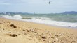 Sea beach and waves in windy day with tourist playing kite surf, low angle view footage