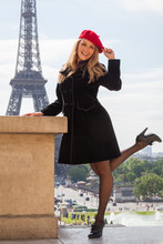 Beautiful Smiling Young Woman, Wearing A Red Beret, In Paris With Eiffel Tower Behind Her.