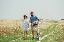 Smiling Couple In Sunglasses With Retro Bicycle In Summer Field With Wild Flowers