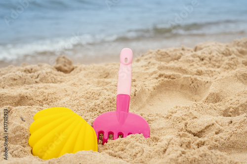 Fotografia  colorful mold and rake on the sand on the beach in summer