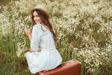 Back View Of Smiling Woman In White Dress With Bouquet Of Wild Camomile Flowers Sitting On Retro Suitcase On Meadow