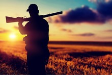 Male Hunter With Rifle On Natural Background