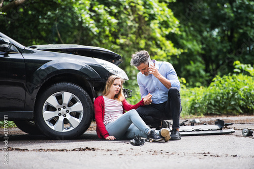 Fotografía Young woman by the car after an accident and a man making a phone call