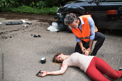 Obraz A man helping a young woman lying unconscious on the road after a car accident. - fototapety do salonu