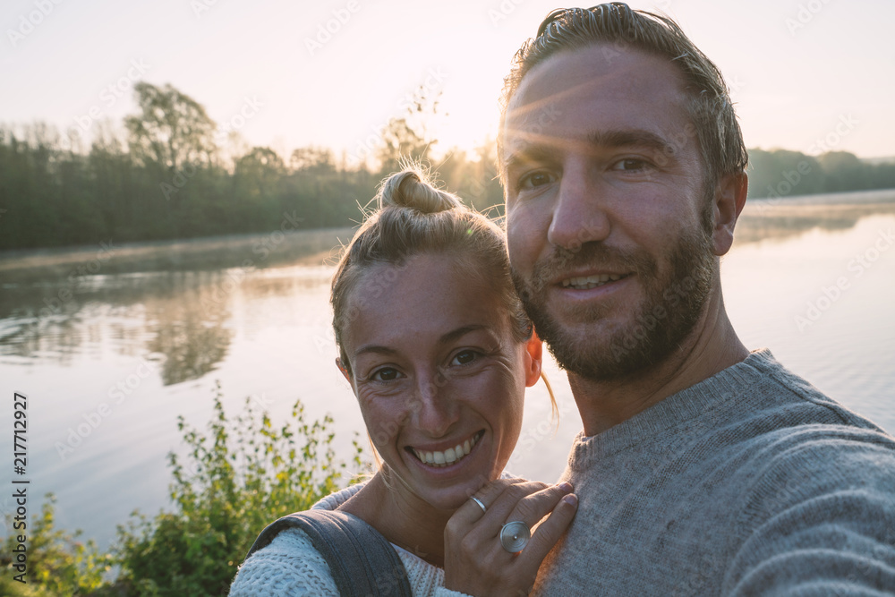 Photo  Young couple taking a selfie portrait by the lake shore at sunrise, sunbeam and reflection on water's surface