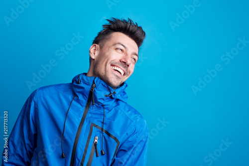 Portrait of a young laughing man in a studio with anorak on a blue background Wallpaper Mural