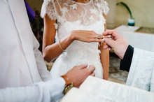 The Priest Blesses Hands With The Wedding Rings Of The Bride And Groom In The Church.