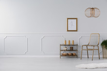 Empty Wall In A Living Room Interior With Golden Accents, Chair, Lamp And Shelf. Real Photo. Place Your Furniture Here