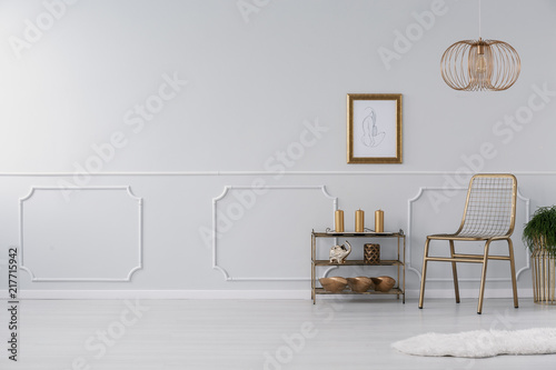 Leinwand Poster Empty wall in a living room interior with golden accents, chair, lamp and shelf
