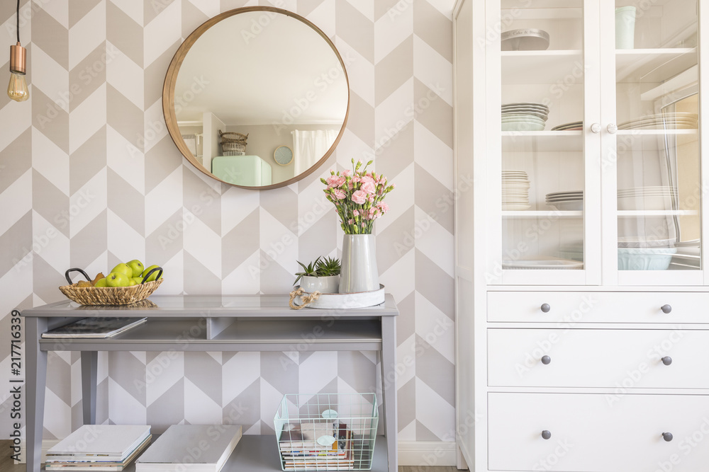 Fototapeta Mirror on patterned wallpaper above grey table with flowers in s