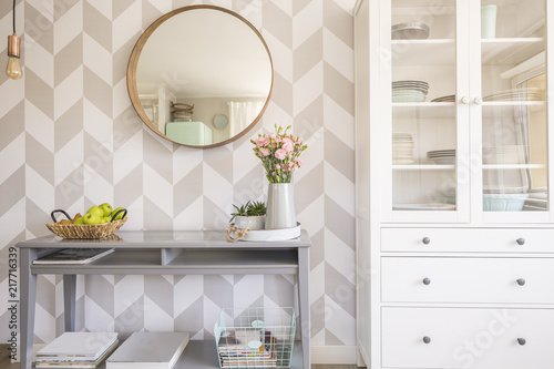 Obraz Mirror on patterned wallpaper above grey table with flowers in s - fototapety do salonu