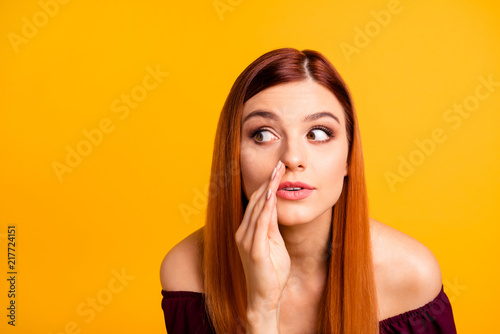 Photo  Close up portrait of  young girl tells a gossip secretly looking