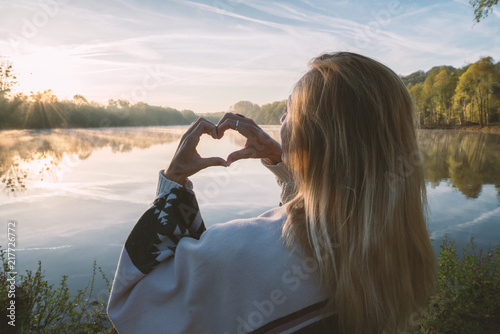 Photo  Young woman standing by the lake at sunrise making a heart shape finger frame on the beautiful landscape, reflection on water