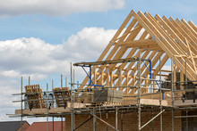 Construction Industry. Timber Framework Of House Roof Trusses With Scaffold Platform And Materials.