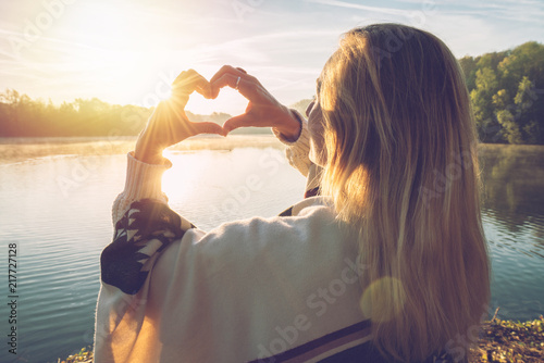 Young woman standing by the lake at sunrise making a heart shape finger frame on the beautiful landscape, reflection on water Canvas Print