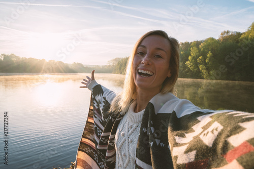 Young woman by the lake at sunrise takes a selfie portrait using mobile phone, beautiful reflection on water surface, model wearing blanket Canvas Print